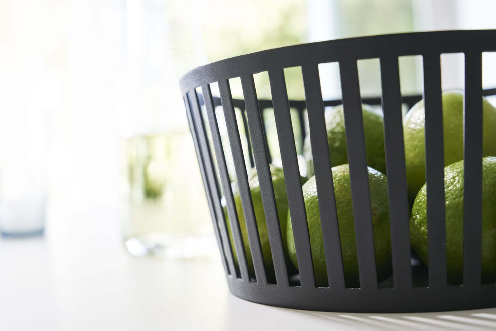 Detailed side view of a black Yamazaki Striped Steel Fruit Basket with limes