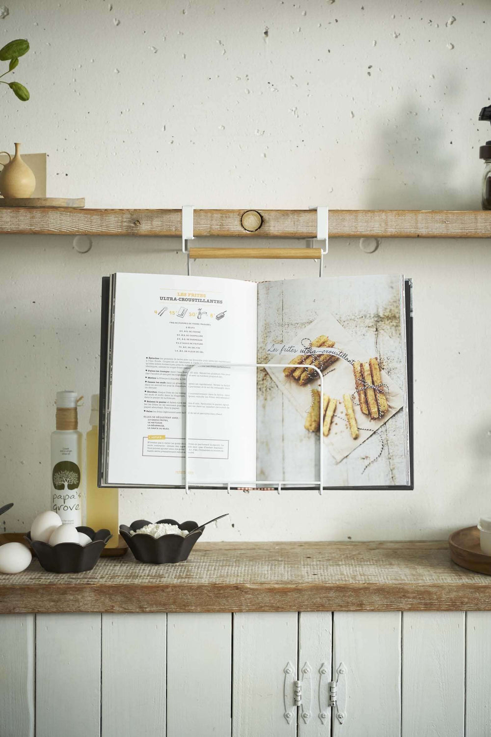 Detailed view of Yamazaki Under-Shelf Tablet and Cookbook Holder, holding a cookbook open