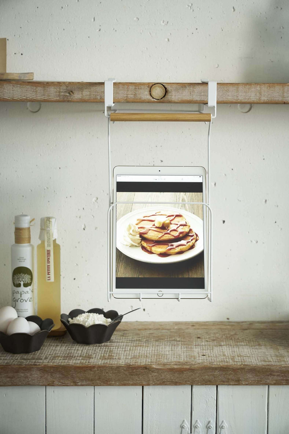 Yamazaki Under-Shelf Tablet and Cookbook Holder attached to a floating shelf above a kitchen counter, holding a tablet that is displaying a recipe image