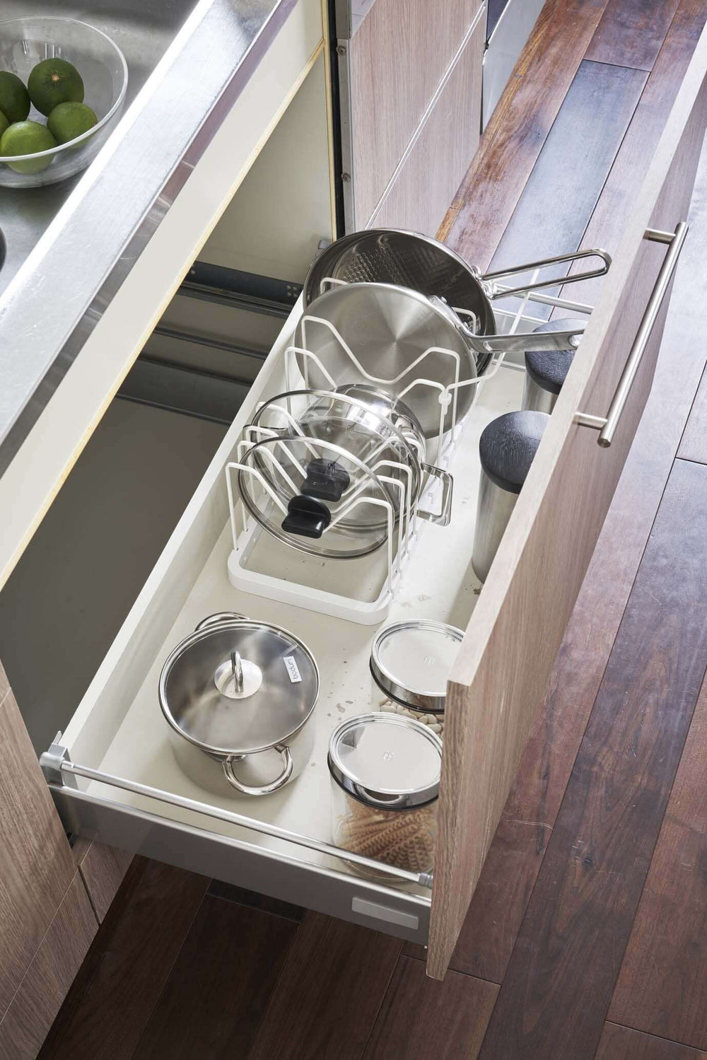 Aerial view of the white lid and pan organizer inside of a large drawer, holding various pans and lids