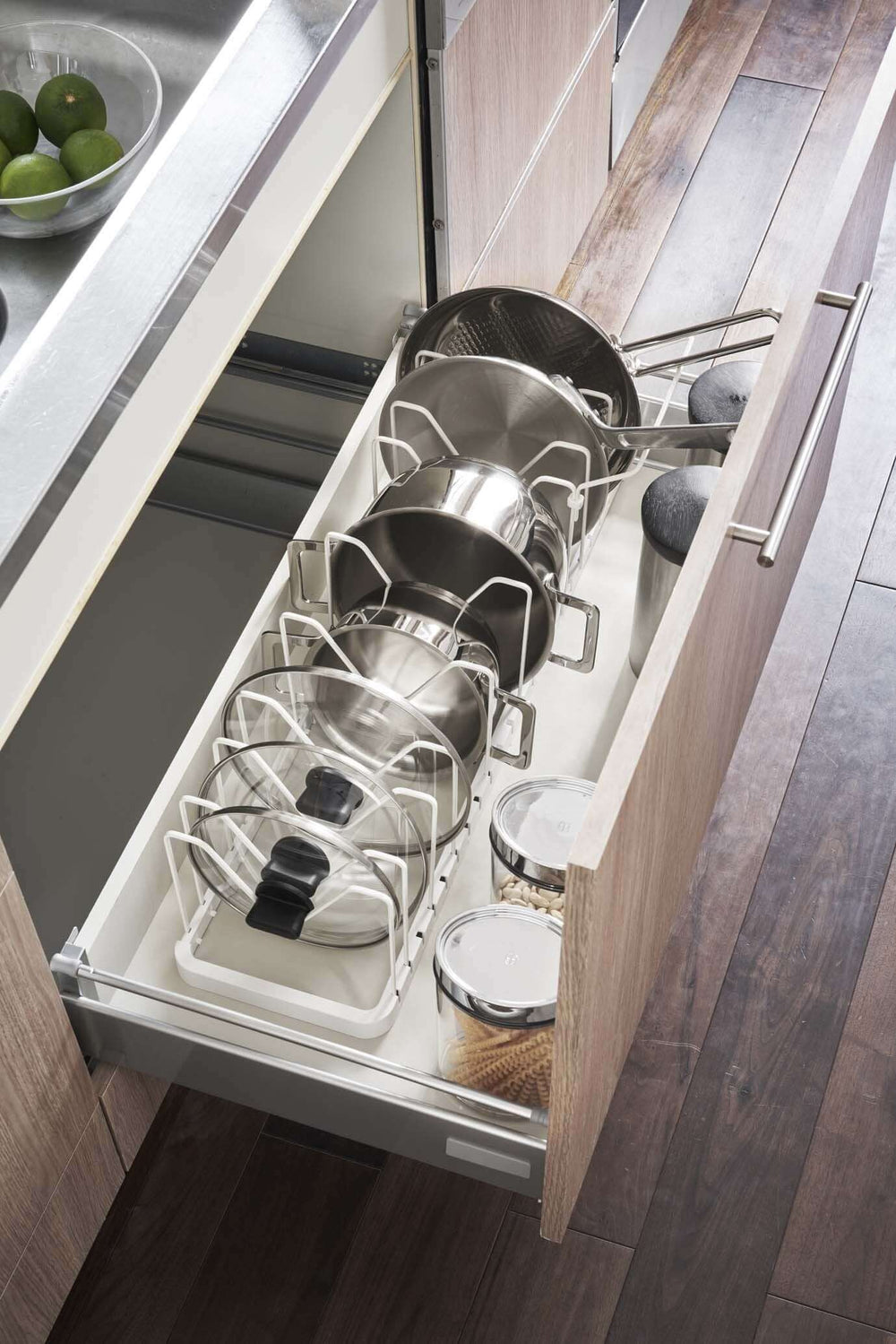 View of the white lid and pan organizer expanded to fill the width of the large drawer and holding more objects
