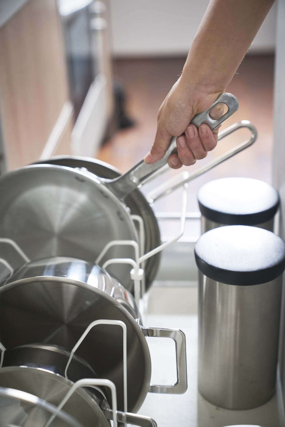 Person easily removing a pan by its handle from the lid and pan organizer