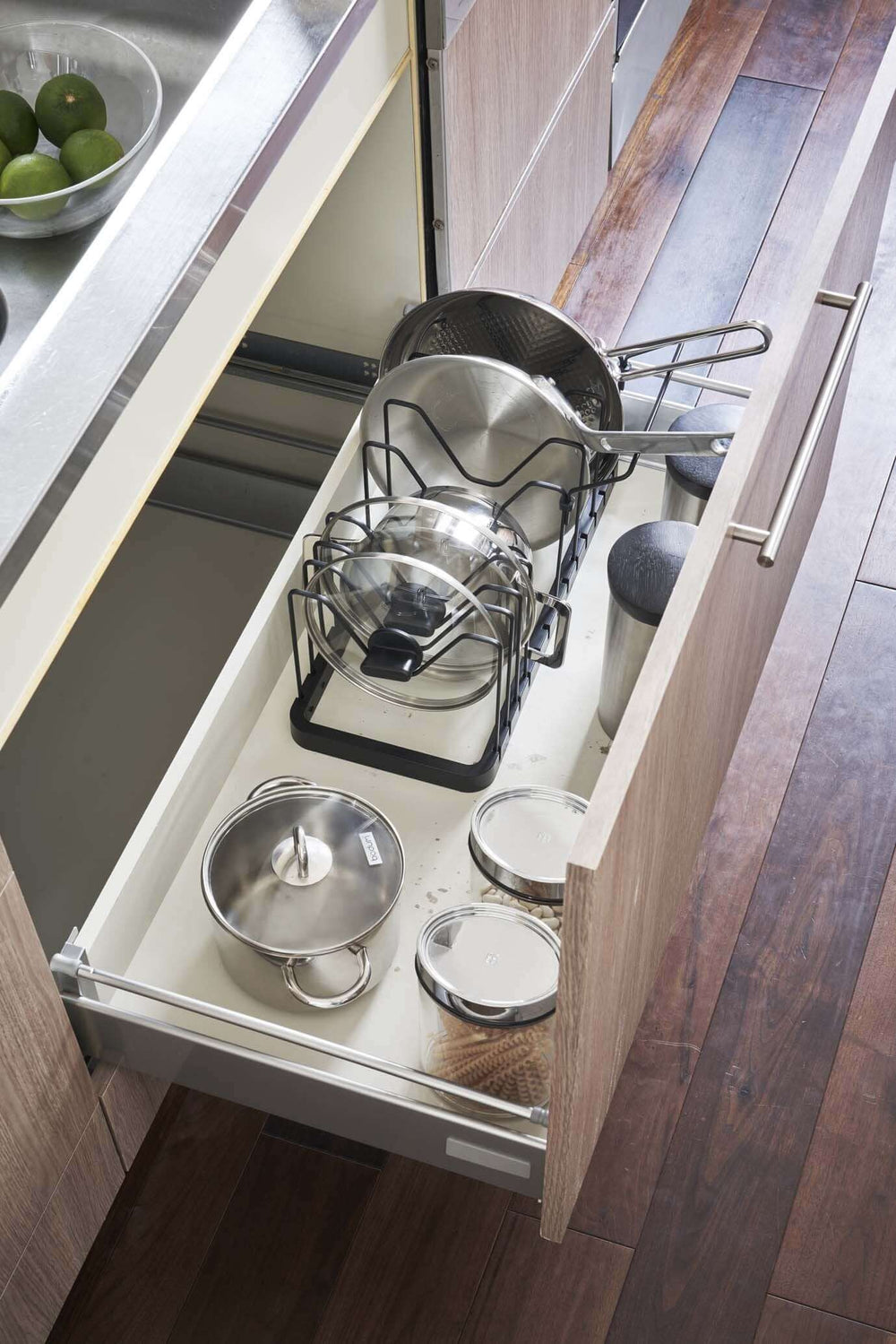 Aerial view of the black lid and pan organizer inside of a large drawer, holding various pans and lids
