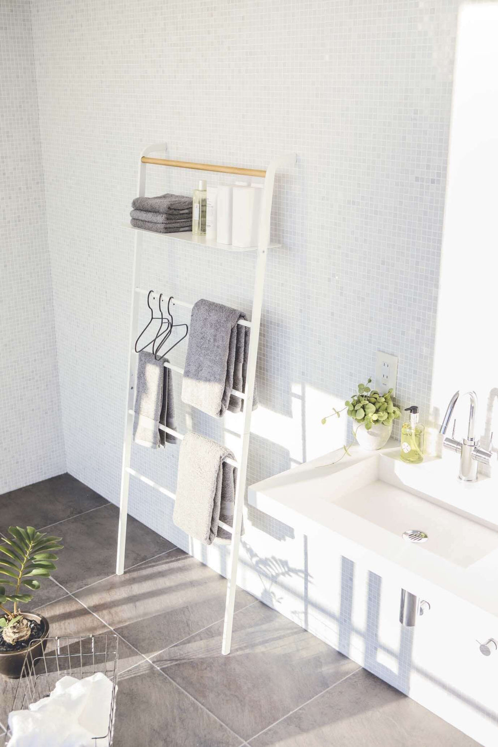 Towels and bath items hanging from white Leaning Ladder in bathroom