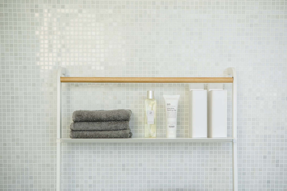 Bath products and folded hand towels on top shelf of white leaning ladder