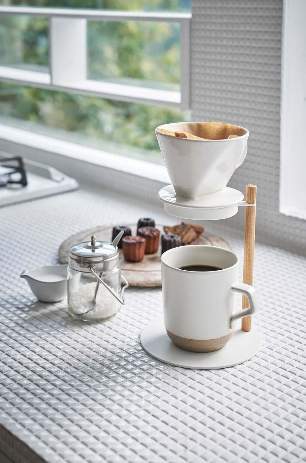 Pour over coffee maker nested in the top of the Yamazaki Dripper Stand, with a coffee mug on the base underneath