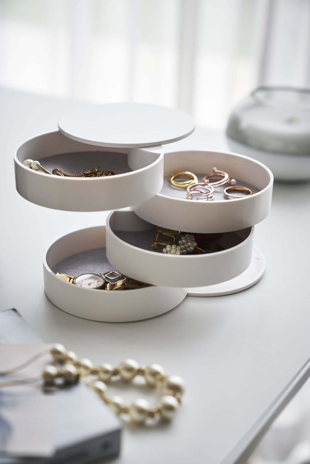 Yamazaki's 4-Tiered Accessory Tray on a table with various jewelry pieces and accessories inside the various stacked round compartments.