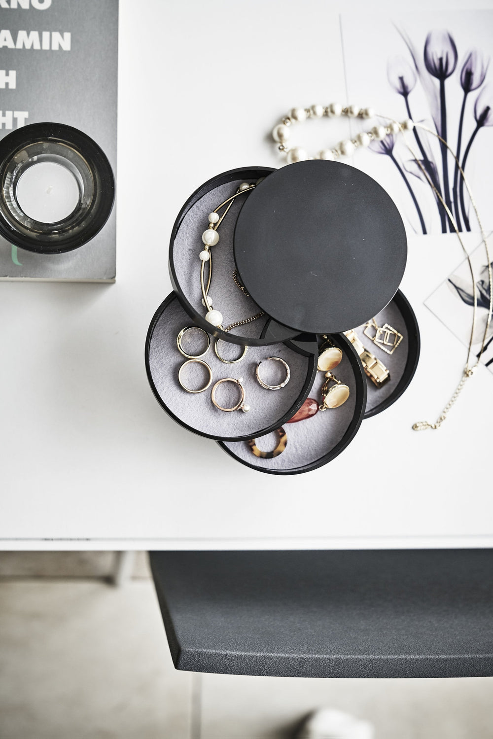 Top view of Yamazaki's 4-Tiered Accessory Tray on a vanity with various jewelry pieces and accessories inside the various stacked round compartments.