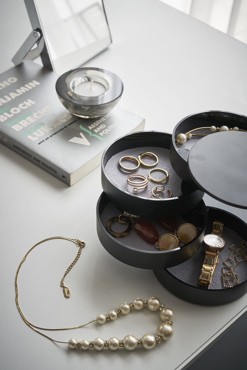 Yamazaki's 4-Tiered Accessory Tray on a desk with various jewelry pieces and accessories inside the various stacked round compartments. Assorted tabletop items appear as well, like a book, necklace, picture frame, and candle.