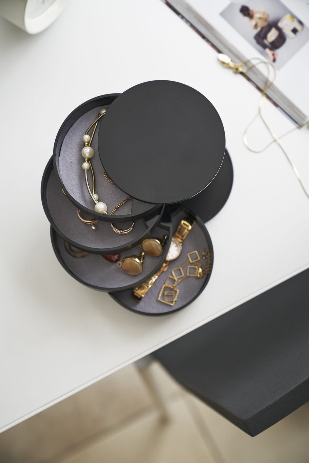 Top, more detailed view, of Yamazaki's 4-Tiered Accessory Tray on a vanity with various jewelry pieces and accessories inside the various stacked round compartments.