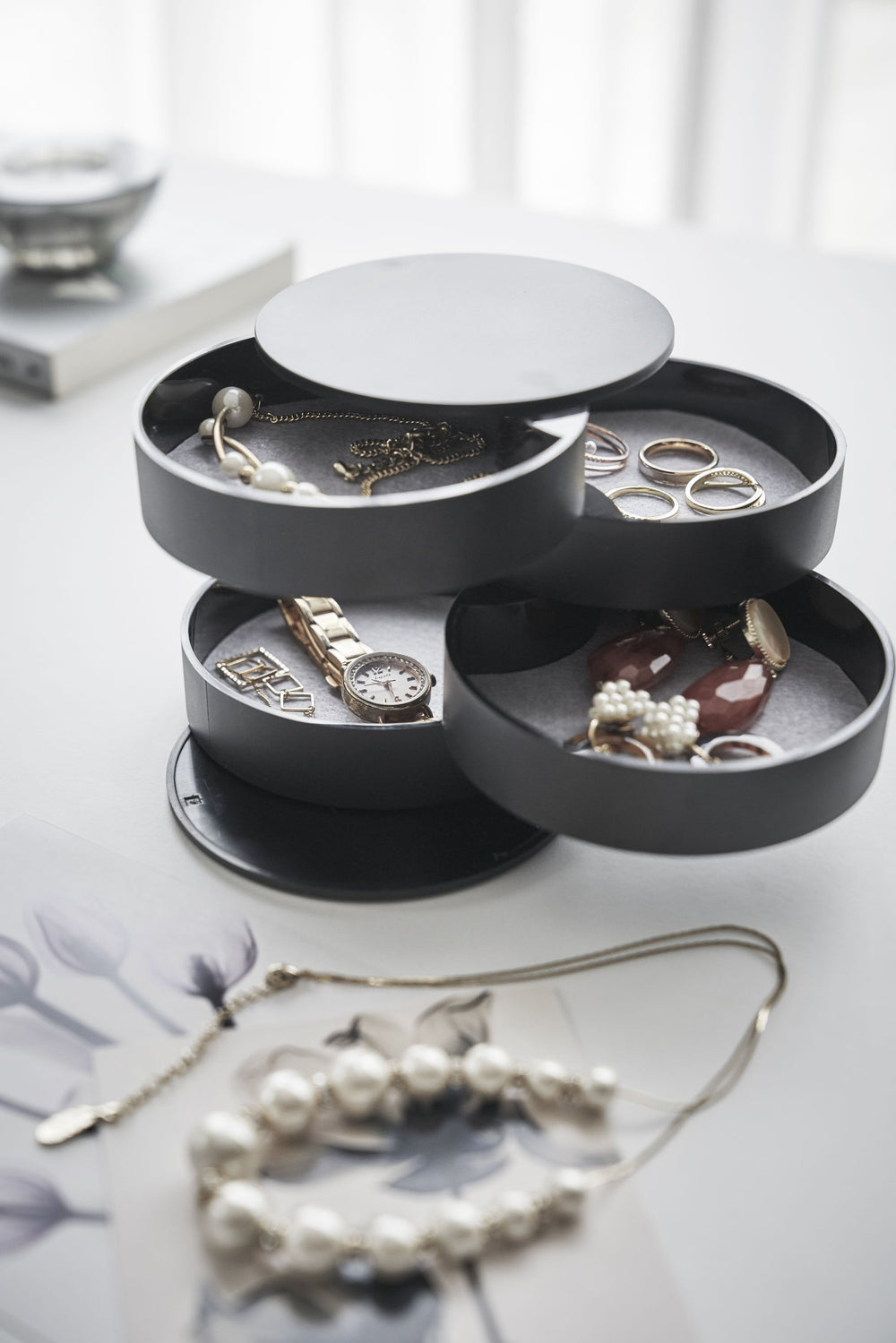 Full, up-close view of Yamazaki's 4-Tiered Accessory Tray on a desk with various jewelry pieces and accessories inside the various stacked round compartments. Assorted tabletop items appear as well, like a book, necklace, picture frame, and candle.
