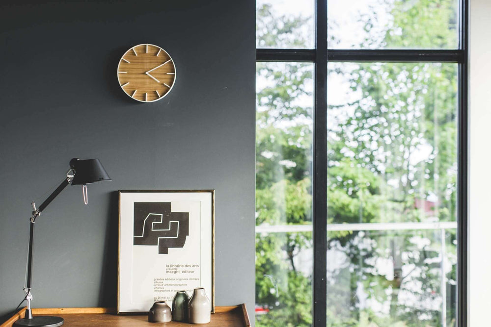Yamazaki Wall Clock with white accents, hanging above a desk with a lamp, art print and decorative vases