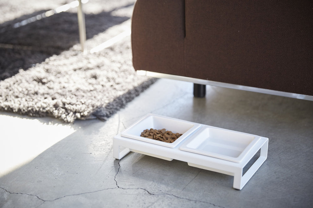 Side angle view of White Yamazaki Pet Food Bowl with Stand in a living room
