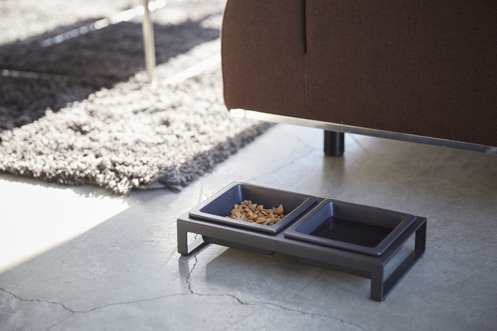 Angled view of black Yamazaki Pet Food Bowl with Stand in a living room