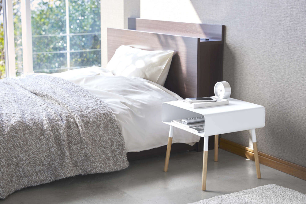Yamazaki Side Table with Storage Shelf in white being used as a nightstand in a bedroom