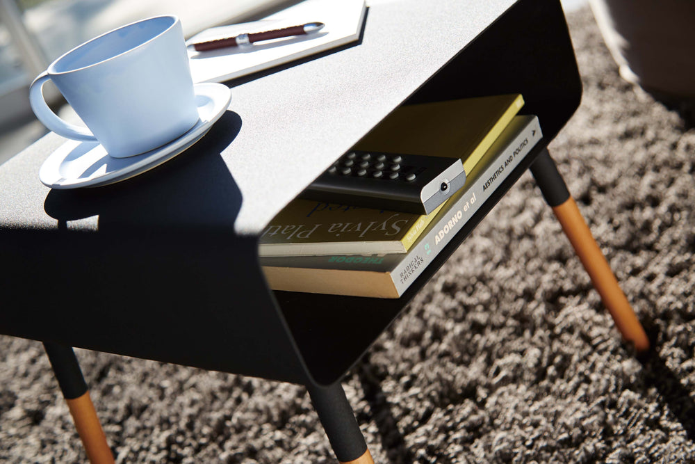 Detail view of the Yamazaki Side Table in black, with books in the Storage Shelf and a cup of coffee and notepad sitting on the tabletop