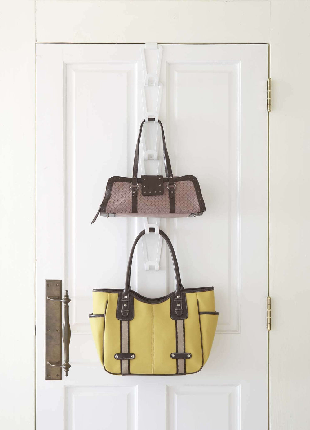 Handbags displayed hanging outside a door using Yamazaki's chain link bag holder.
