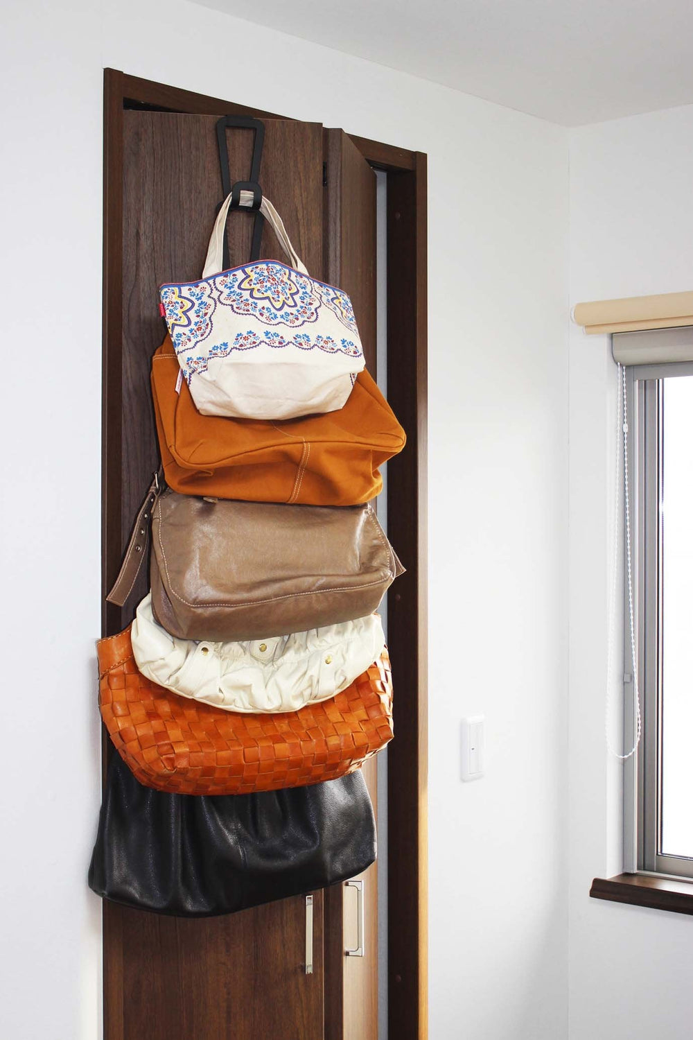 Yamazaki's Black chain link bag hanger displaying bags hung on a wooden closet door.