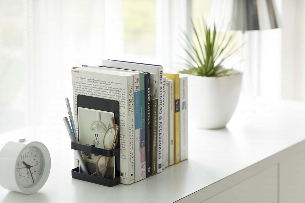 Black Yamazaki bookend with storage compartment holding a stack of novels on a windowsill.