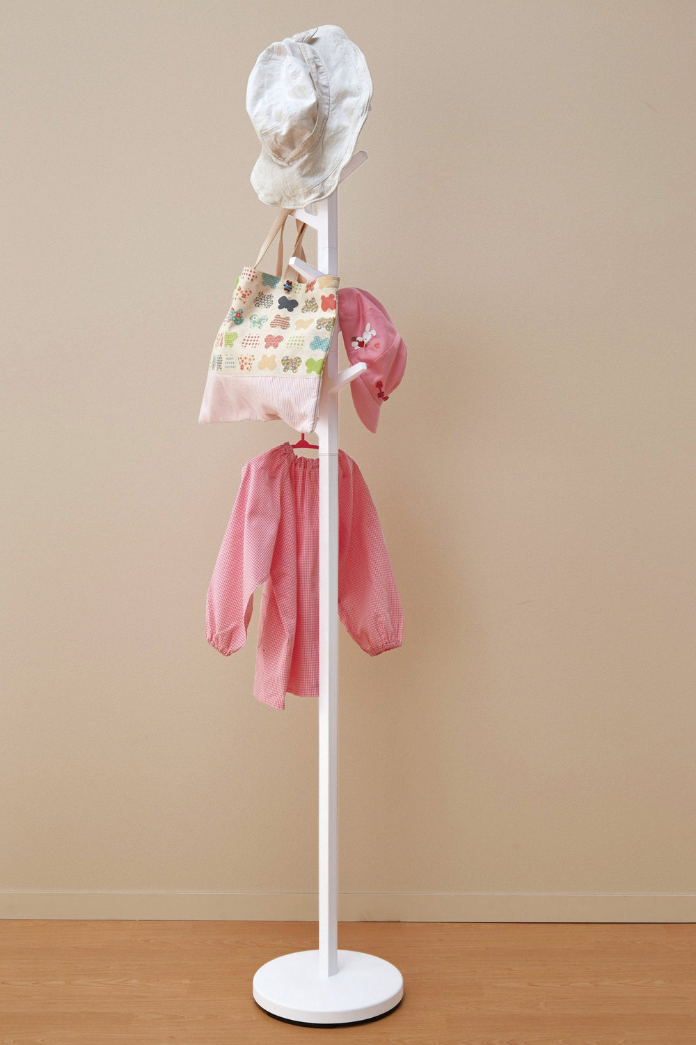 White coat rack in the shape of a tree hung with children's clothes and hats.