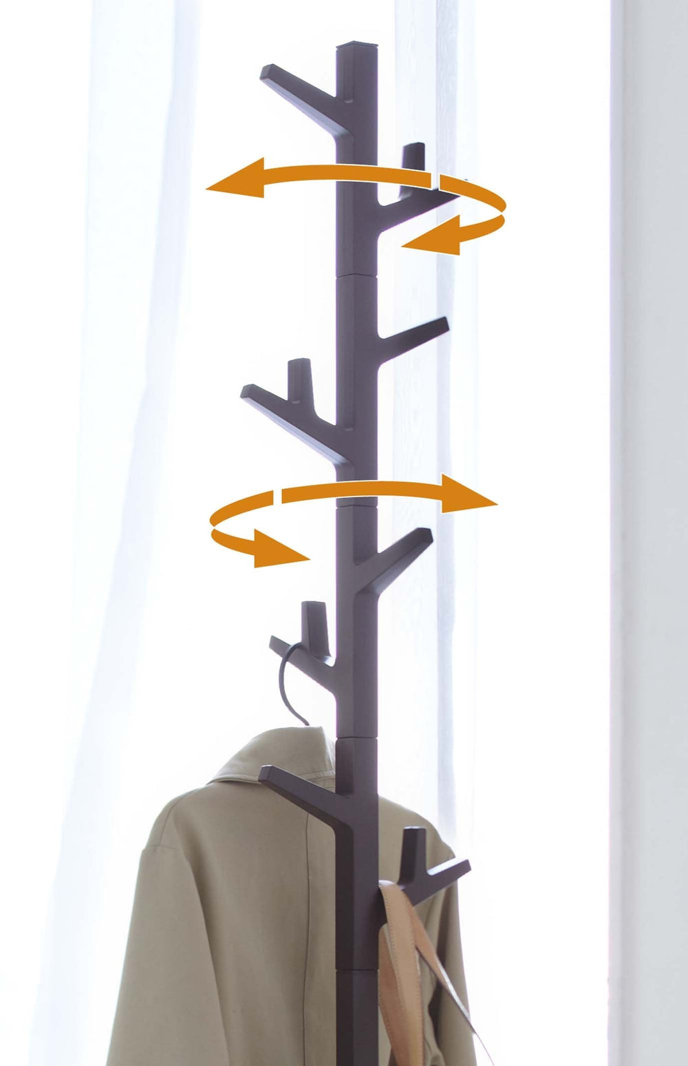 Yamazaki's Brown coat rack in the shape of a tree marked with orange arrows to indicate its mobility
