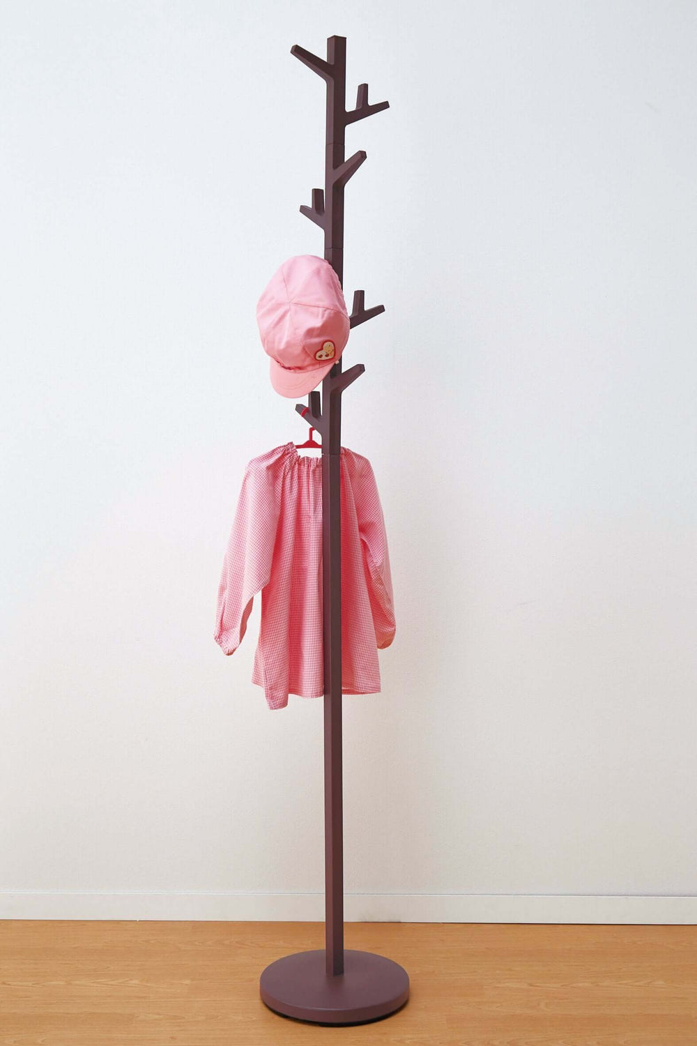 Yamazaki's Brown coat rack in the shape of a tree, hung with pink children's clothes.