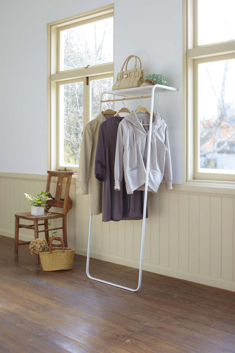 Yamazaki's white leaning coat rack hung with coats. Handbags and accessories sit on a top shelf.