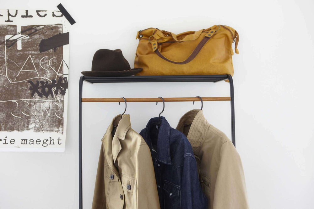 Yamazaki's black leaning coat rack hung with coats in a bedroom. Handbags and accessories sit on a top shelf