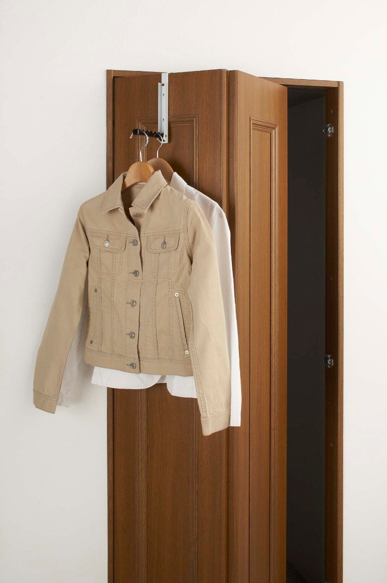 Yamazaki's folding hook on a door holding clothes.