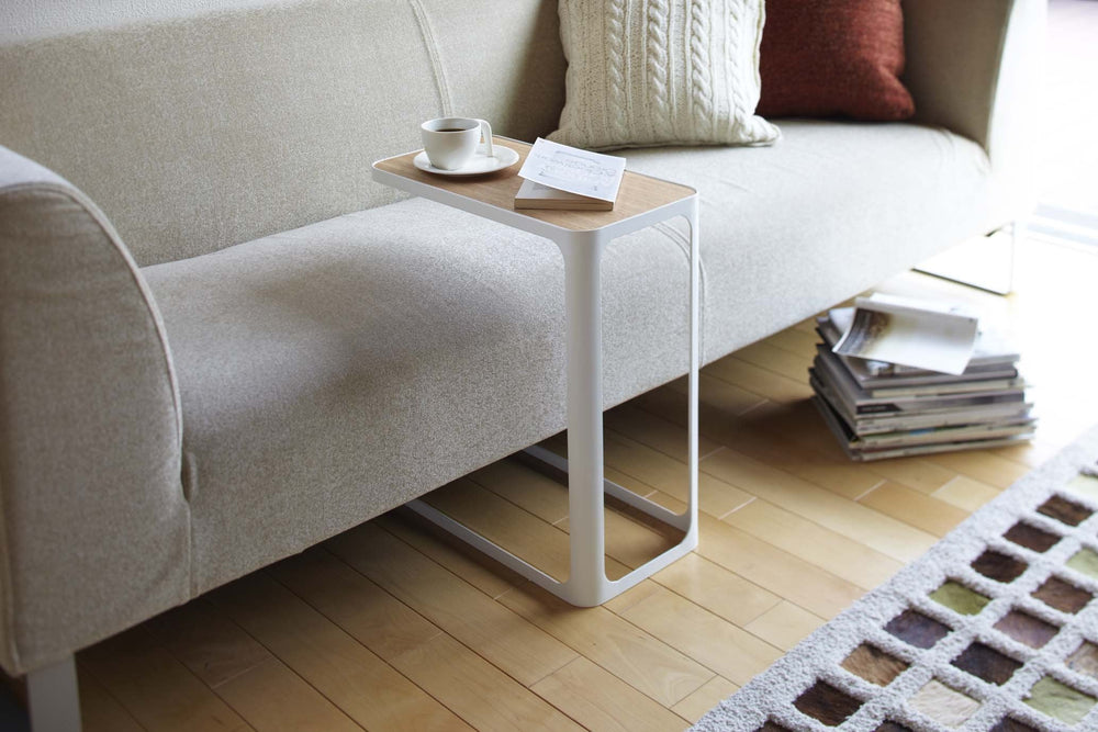 Yamazaki's White accent table with wood top nestled over a modern gray sofa.