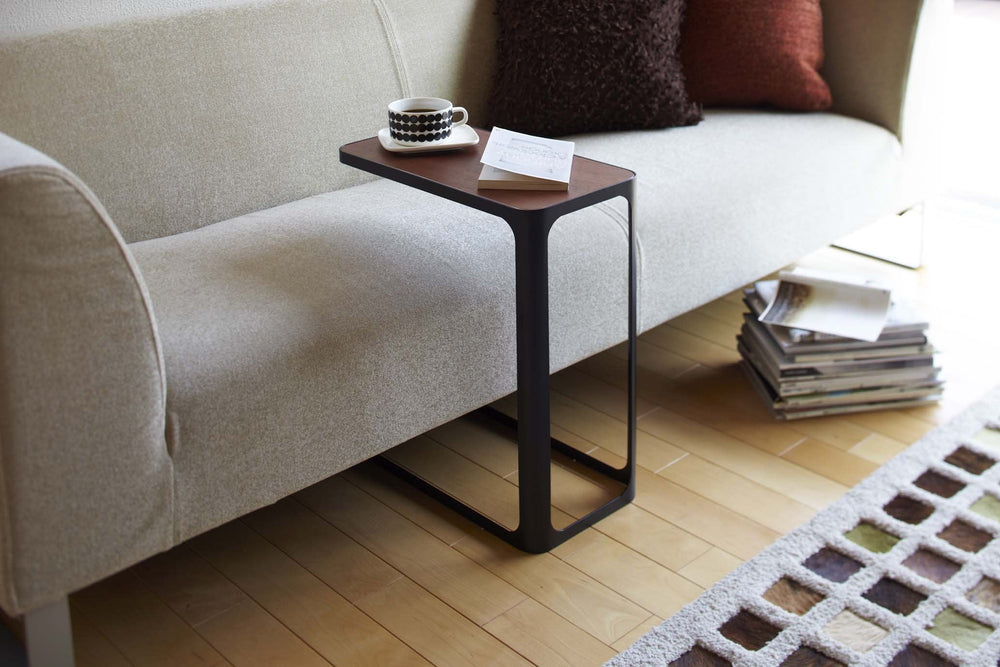 Black accent table with wood top nestled over a modern gray sofa