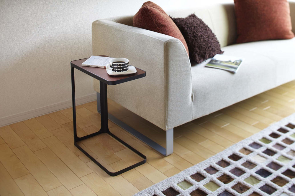 Black accent table with wood top sitting next to a modern gray sofa.