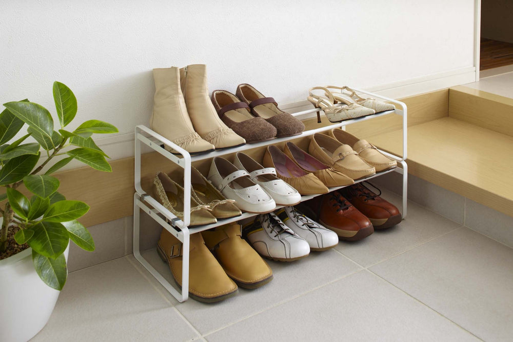 White shoe rack holding brown and white shoes next to plant and staircase.