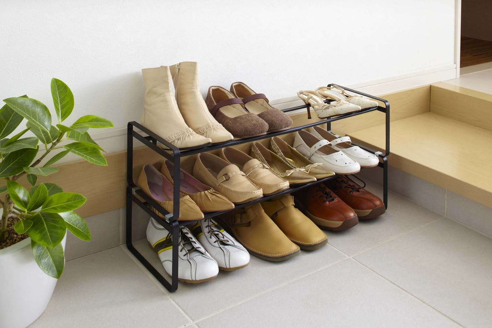 Two simple black shoe racks by Yamazaki stacked and filled with brown and white shoes next to a plant