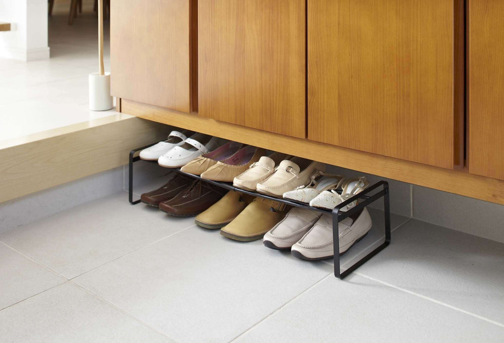 Simple black shoe rack by Yamazaki under a brown cabinet.