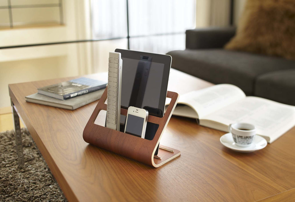 Yamazaki's dark plywood stand holding a mobile tablet and remotes on a coffee table