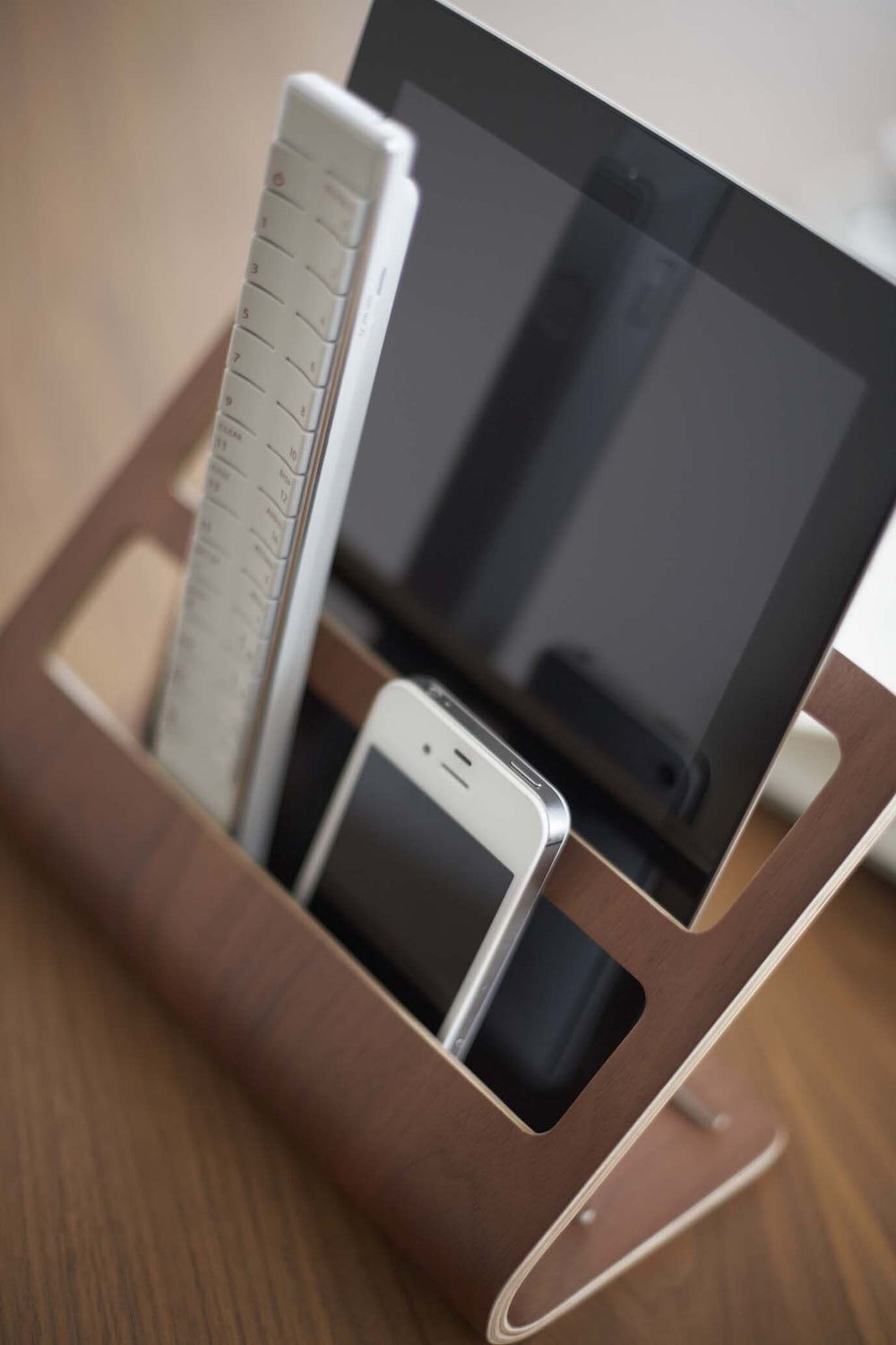 Yamazaki's dark plywood stand holding a mobile tablet and remotes on a coffee table.