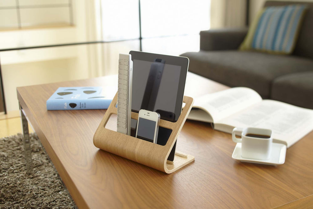 Yamazaki's light plywood stand holding a mobile tablet and TV remotes on a coffee table.