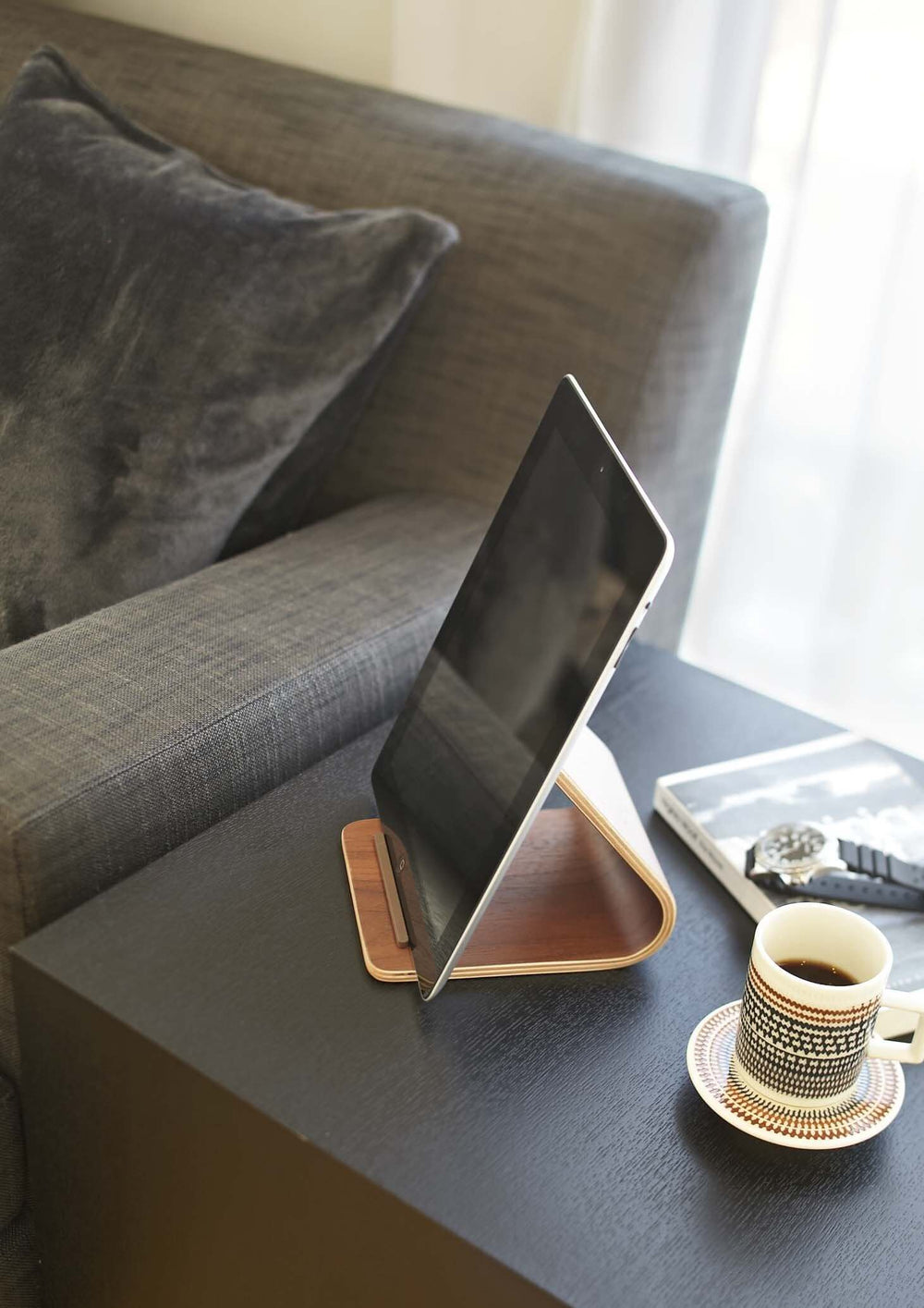Yamazaki's plywood stand holding a tablet on a side table next to the sofa.