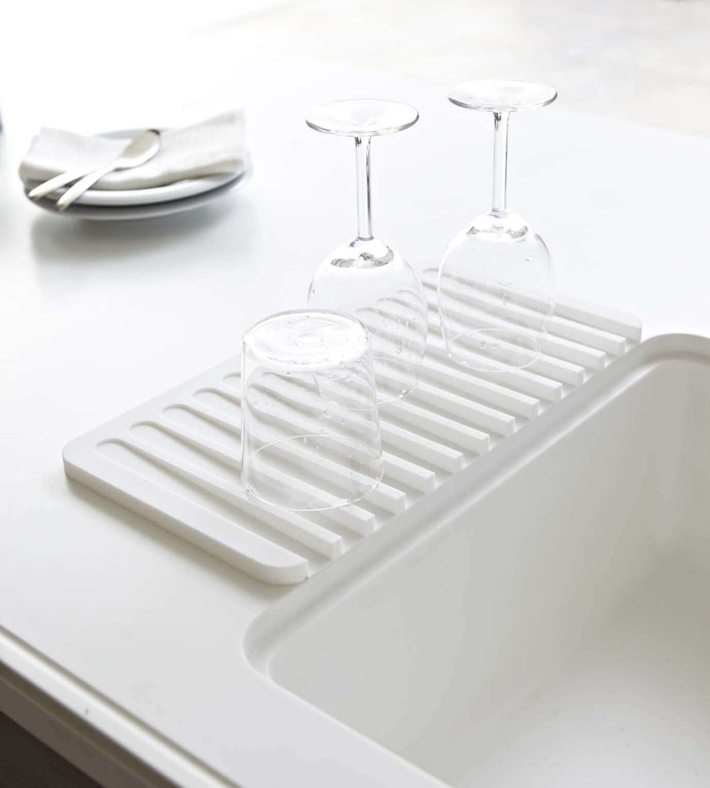 Wineglasses drying on top of Yamazaki's white silicone dish drainer tray