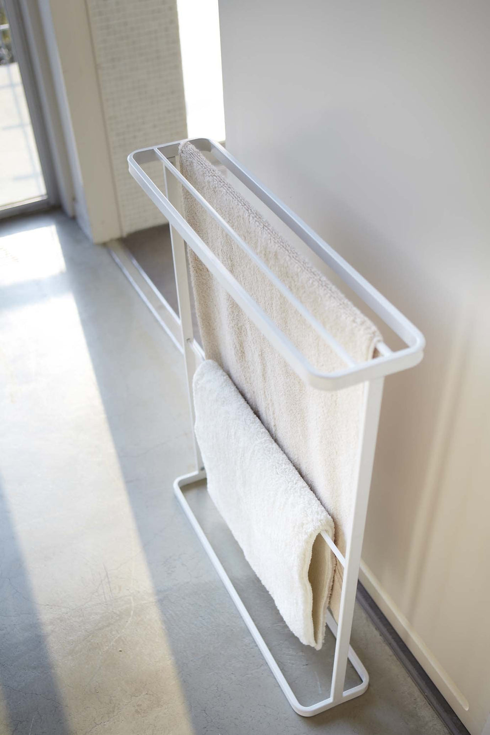 Yamazaki's White towel rack shown from above hung with two towels