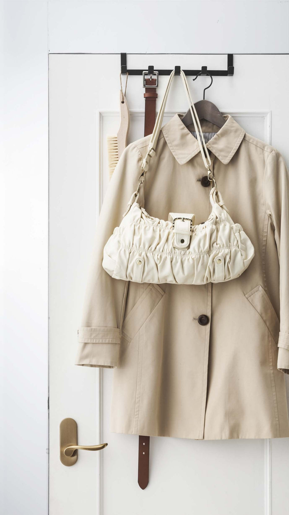 Yamazaki's wide over-door hook with five hooks hanging on a door and holding handbag and coat.
