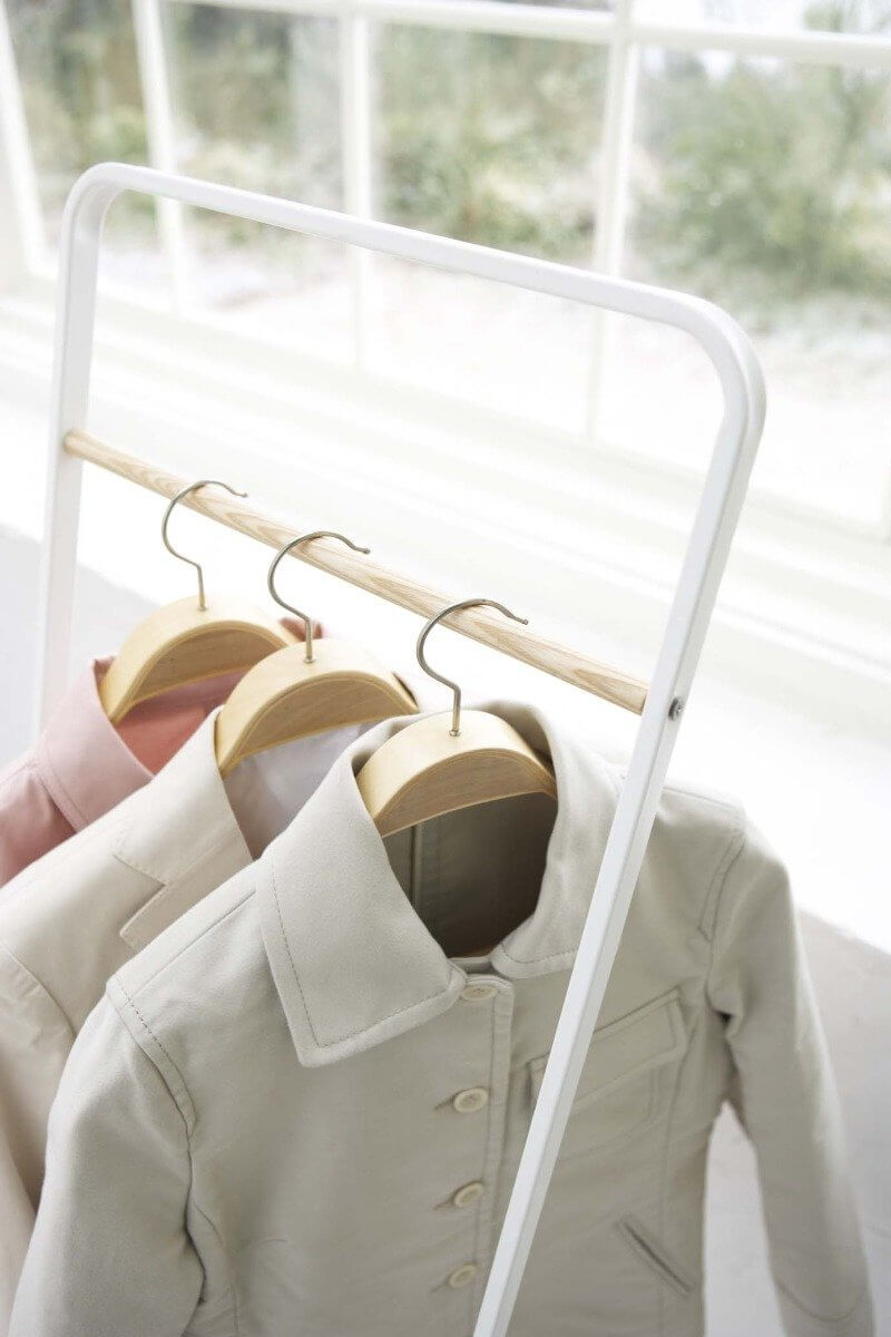 Yamazaki's White standing rack with wood accent bar hung with small jackets in a bright room.