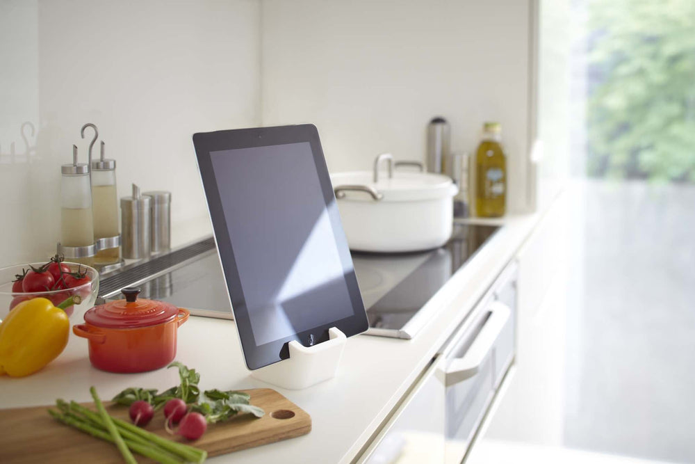 Yamazaki's white silicone cube holding a mobile tablet on a kitchen countertop surrounded by chopped vegetables.