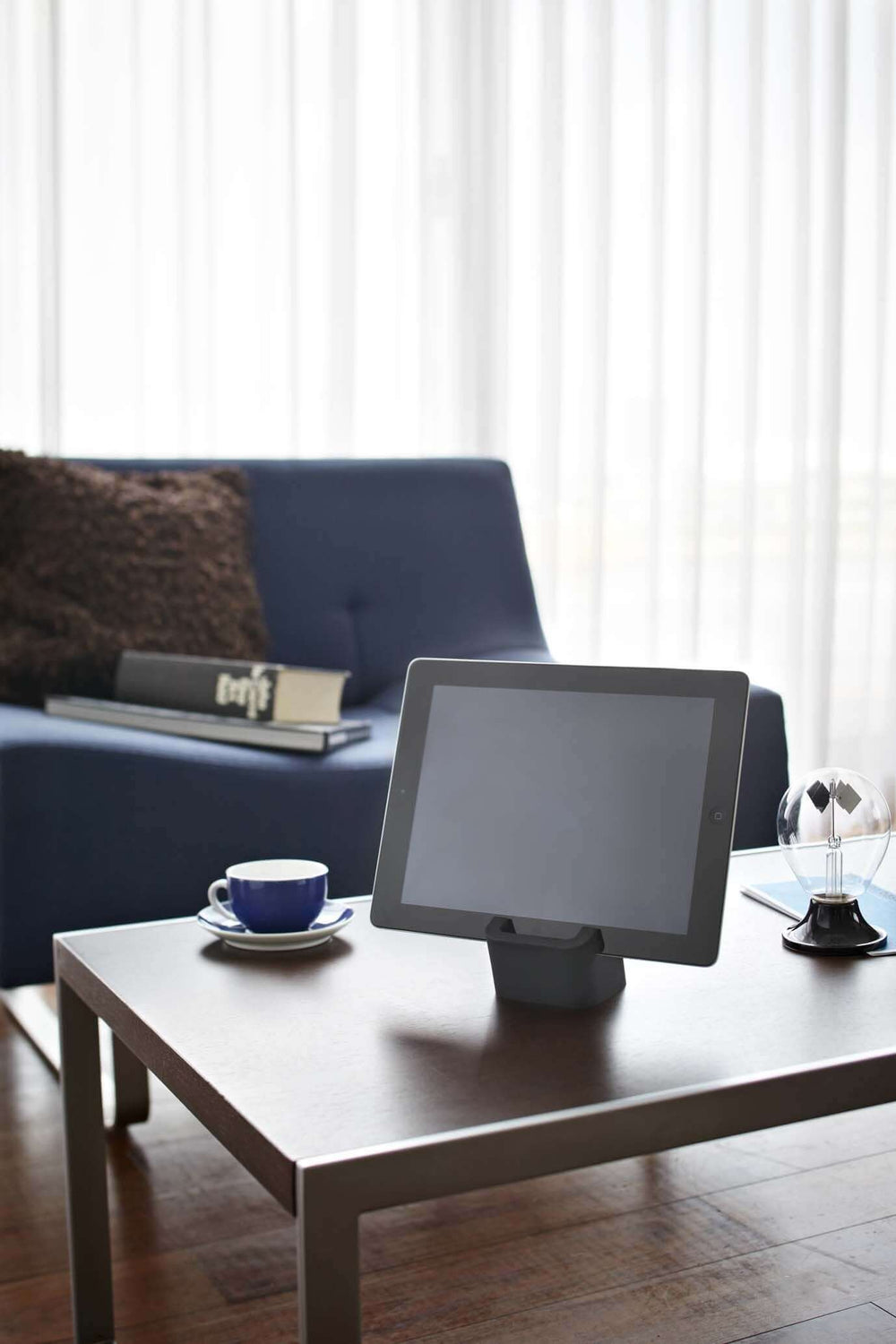 Yamazaki's black silicone cube holding a mobile tablet on a coffee table in living room