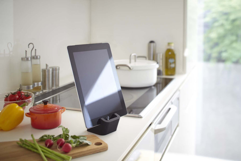 Yamazaki's black silicone cube holding mobile tablet on a kitchen countertop surrounded by chopped vegetables.