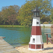 Octagonal Amish-Made Wooden Montauk, NY Replica Lighthouse on the edge of a lake next to a pier
