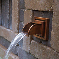 Atlantic Water Gardens Copper Finish Mantova Wall Spout set within patio hardscape