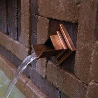 Atlantic Water Gardens Copper Finish Verona Wall Spout set within patio hardscape