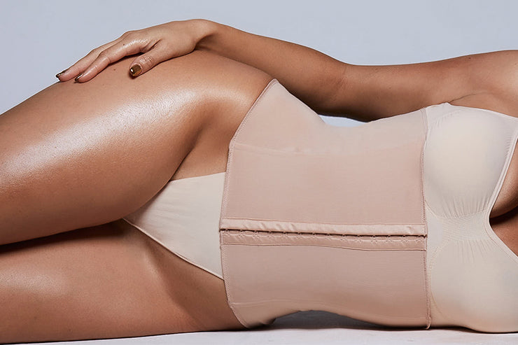 A SKIMS Model lays on her side wearing the Sculpting Waist Trainer in Clay